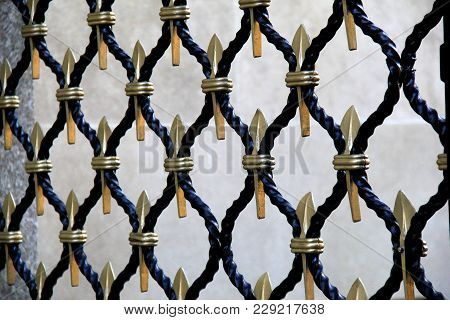 Horizontal Background Of Black Metal Fencing With Gold Pattern Running Throughout.