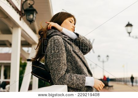 A Nice Young Dark-haired Girl In A Gray Coat And Glasses Walks Along The Embankment In Cloudy Weathe