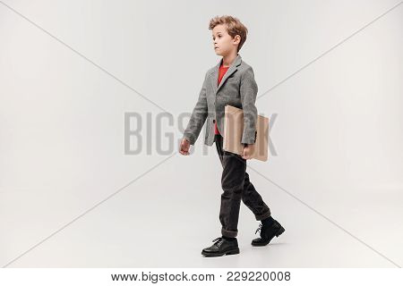 Stylish Little Schoolboy Walking With Big Book Isolated On Grey