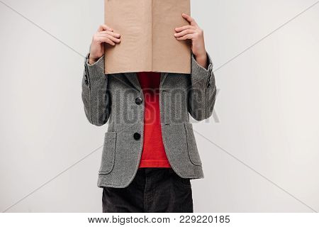 Little Schoolboy Covering Face With Book Isolated On Grey