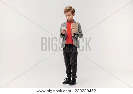 Stylish Little Schoolboy With Smartphone And Book Isolated On Grey