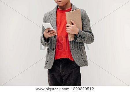 Cropped Shot Of Stylish Little Schoolboy With Smartphone And Book Isolated On Grey