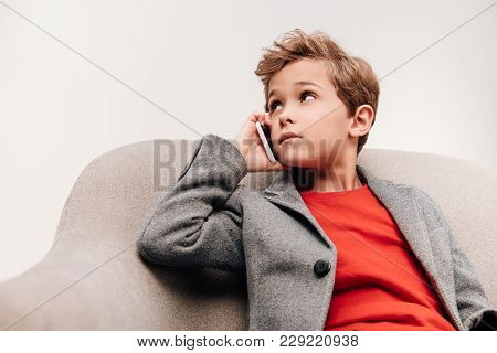 Stylish Little Boy Talking By Phone While Sitting In Armchair Isolated On Grey