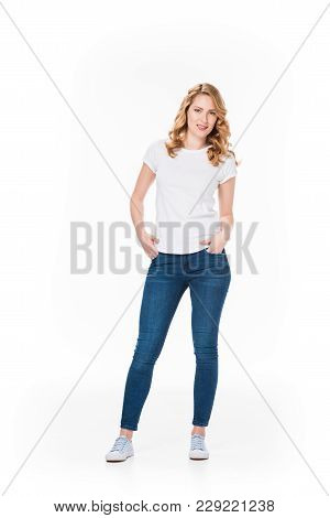 Smiling Blond Woman With Hands In Pockets Looking At Camera Isolated On White