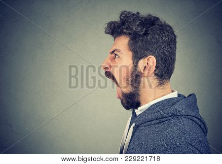 Side View Of Casual Hipster Beard Man Yelling In Madness Looking Away.