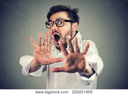 Young Scared Man In Shirt Holding Hands In Front Of Face And Screaming In Panic.