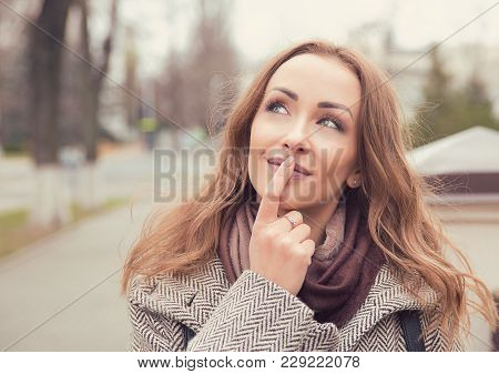 Young Pretty Woman In Coat Touching Lips And Daydreaming While Standing On Street And Looking Away.