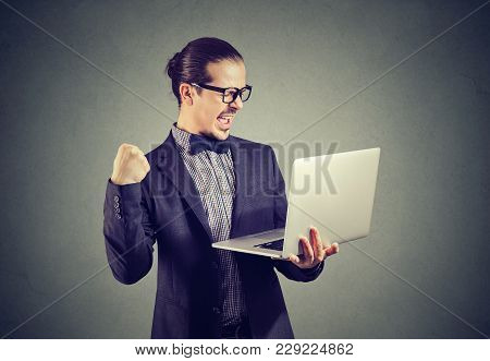 Excited Young Man Holding Laptop And Looking Happy Winning With Fast Upgrade.