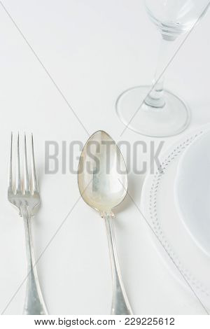 White Vintage Empty Plates Unpolished Silver Fork Spoon Wine Glass On Concrete Tabletop. Minimalist