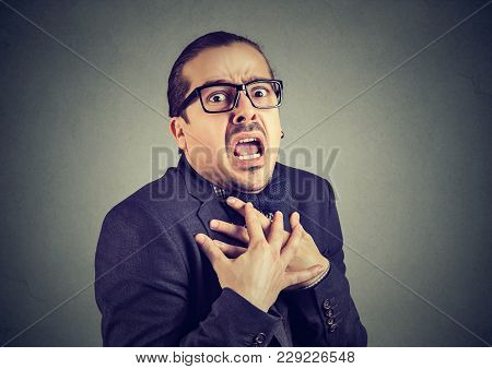 Young Man In Formal Clothing Having Panic Attack While Posing On Gray.