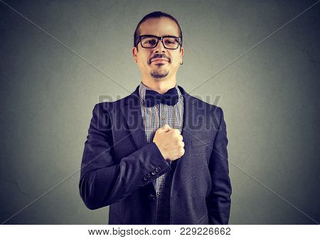 Young Businessman Looking Extremely Proud Posing With Hand On Chest Looking At Camera.