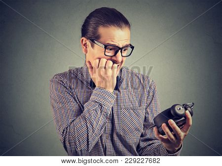 Young Man In Eyeglasses Looking Nervously At Clock Feeling Pressure Of Lack Of Time.