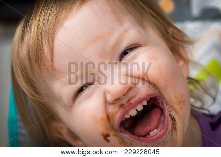A Toddler Laughing After Eating Some Chocolate