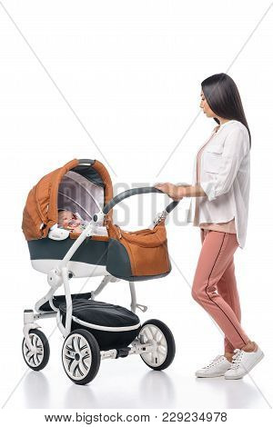 Young Woman Looking At Infant Baby In Baby Carriage Isolated On White