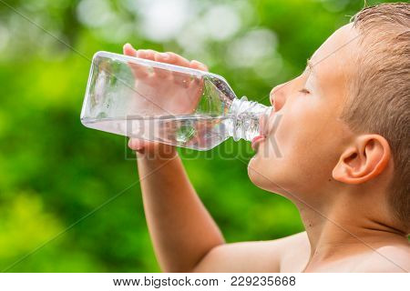 Closeup Of Young Boy Drinking Pure Tap Water From Transparent Plastic Drinking Bottle While Outdoors
