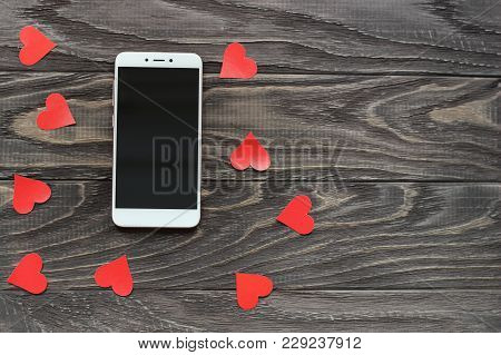 The Mobile Phone Is White In Color Against The Background Of A Tree And Next To A Small Red Heart. V