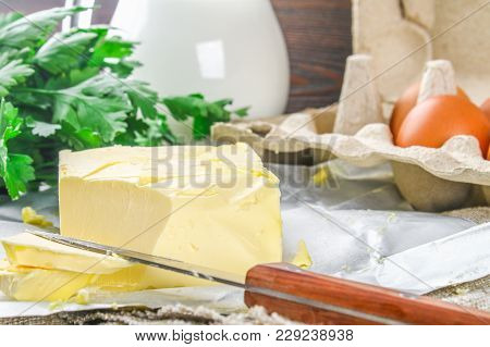 A Bar Of Butter Is Cut Into Pieces On A Wooden Board With A Knife, Surrounded By Milk, Eggs And Pars