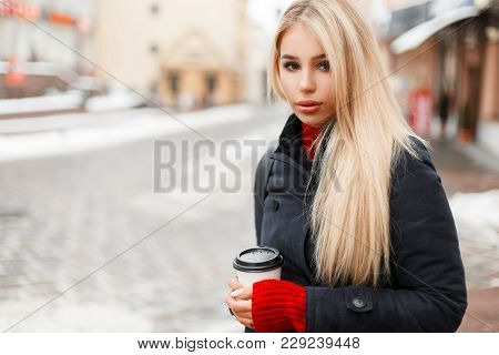 Young Beautiful Fashion Woman With Coffee In A Trendy Vintage Coat Is Traveling In The City