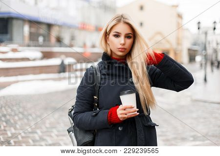 Beautiful Fashionable Woman With A Cup Of Coffee In A Stylish Trendy Coat With A Bag Is Traveling In