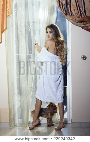 Lady with pensive face in bathrobe with nude shoulders. Girl enjoys morning near window with her cute dog. Sexy nude woman with long hair looks hot and desire. Attraction and desire concept. poster