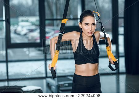 Beautiful Young Sporty Woman Working Out With Suspension Straps At Gym