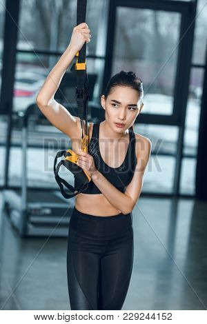 Young Sporty Woman Working Out Relaxing At Gym While Leaning On Suspension Straps