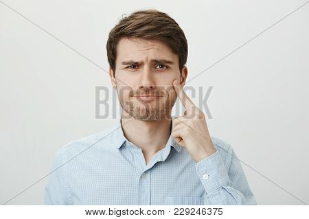 Unimpressed Handsome Bearded Guy Showing His Indifference And Pointing At Cheek As If Pointing At Te