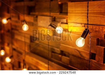 Hanging Light Bulb Over The Wooden Background, Mockup Poster. Background Wood Planks With Lamps