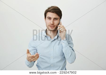 Do You Agree Or Not. Handsome Confident Caucasian Male In Ordinary Blue Shirt Talking On Smartphone