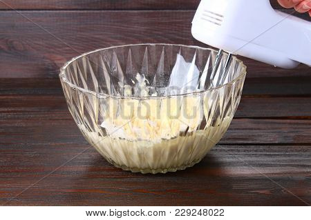 Mixer In Hand Stirring Dough For Muffins On A Wooden Table
