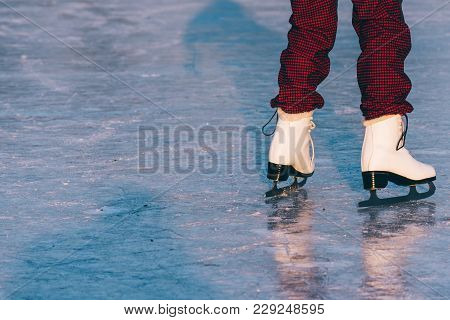 Close-up Of Woman Skating On Ice. Close-up Of Skates And Ice. Beautiful Winter Day.
