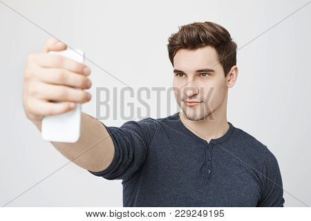 Handsome Caucasian Young Male With Dark Hair, Appealing Eyes And Stubble Holding Mobile Phone, Posin
