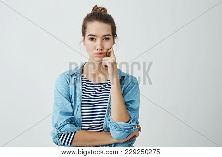 Girl Need To Find Answer. Charming Young Caucasian Woman With Bun Hairstyle Holding Fingers On Cheek