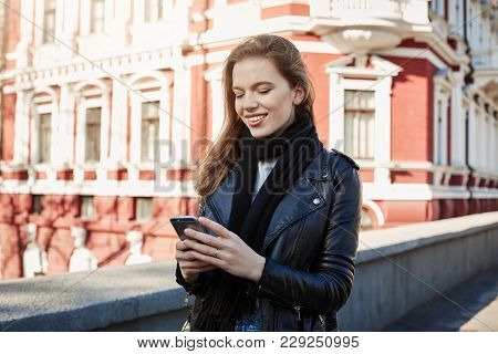Big City Life. Portrait Of Charming Stylish Girl Standing On Street, Holding Smartphone And Texting