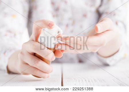 Young Woman Hands Applying Moisturizing Cream To Her Skin