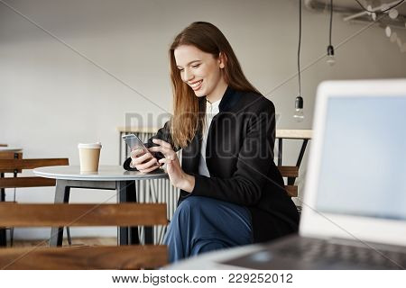 Guy With Laptop Gazing At Attractive Woman Sitting Next To Him In Cafe. Side-shot Of Beautiful Styli