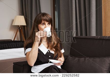 Cup Of Coffee For Housemaid Of Year. Portrait Of Dreamy Neat Maid In Uniform Sipping Tea While Looki
