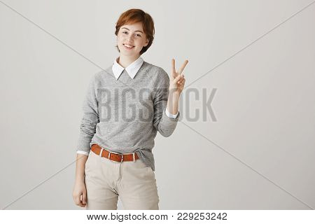 Portrait Of Attractive Boyish Charismatic Women In Trendy Formal Outfit Showing Peace Or Victory Sig