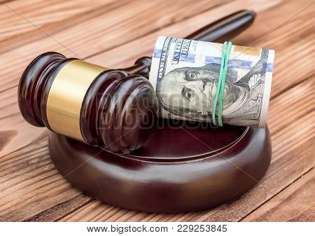 Judge's Gavel With Rolled Dollar Bills On The Table.