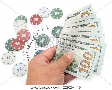 Casino Chips And Cards And One Hundred Dollars On A White Background .
