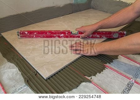 Workers Hands With Ceramic Tiles And Tools For Tiler. Floor Tiles Installation. Home Improvement, Re