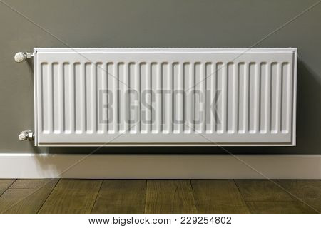 White Heating Radiator On Wall In An Apartment With Wooden Floor