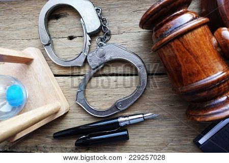 No One Is Above The Law Concept With Judge Hammer Near Handcuffs On Wooden Background