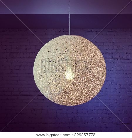 Pendant Lamp With Round Lampshade In Purple Tones, On Brick Wall Background.