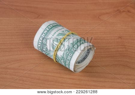 A Roll Of One Dollar Money On Wooden Table.