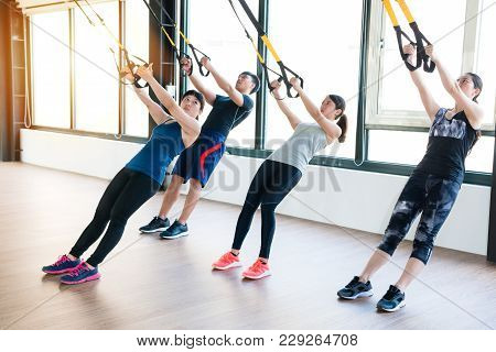 Team Of Asian People Training With Trx