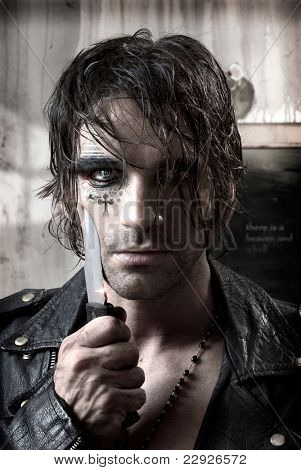 Sexy portrait of a dangerous man holding knife with fashion makeup on face