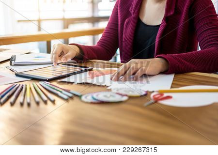 Close Up Of Woman Fashion Designer At Work Drawing Sketches For Clothes In Atelier With Tailor Tool