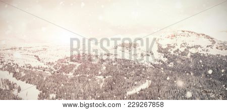 Snow falling against scenic view of snow capped mountain
