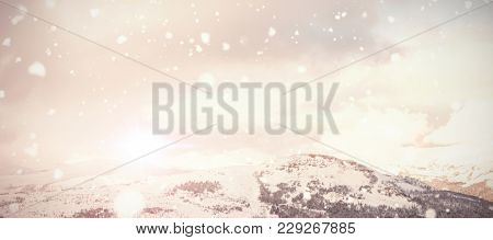 Snow falling against scenic view of snow mountains
